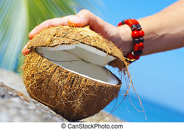 crack it - View of a woman opening big coconut in tropical...