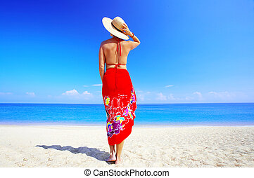 woman in red - view of female back on a background of the...