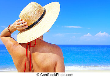 holding hat - view of female in sailor-hat on a background...