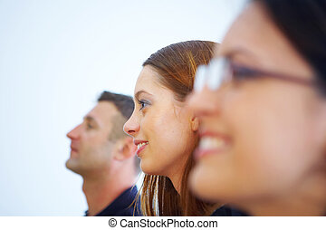 three - two woman one male profiles view in a row smiling in...
