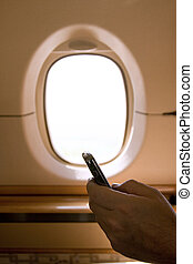 Person Holding a Business Phone While on a Plane