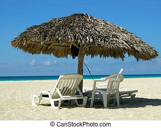 Varadero beach Cuba - Straw sun shelter and beach chairs at...