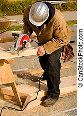 Sawing - A construction worker cutting a piece of lumber...