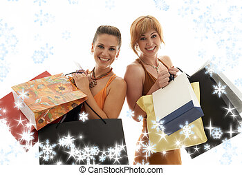 shopping girls with snowflakes - two happy girls with...