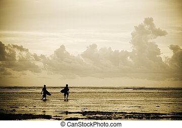 Surfers on the beach - A silhouette shot of a couple of...