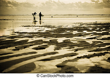Surfers at the beach - Two surfers at the beach during...
