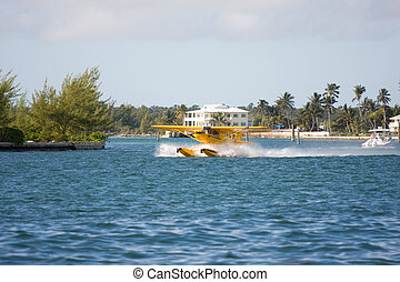 take off - small yellow seaplane taking off close to shore
