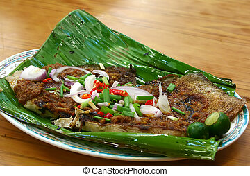 BBQ stingray on banana leaf garnished with spring onions,...
