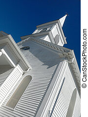 wooden church spire against deep blue sky, vertical