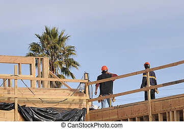 hispanic carpenters working on an apartment building under...