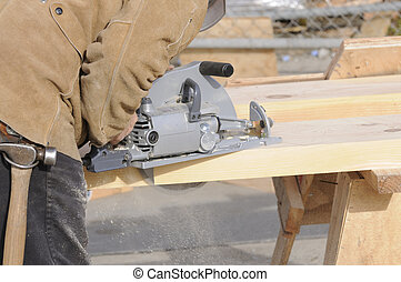 Carpenter cutting steps into a 4x12 stringer for a...