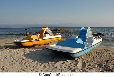 blue and yellow pedalos - two blue and yellow pedallos on a...