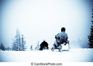 Winter sport - A shot of people riding snowmobile in the...