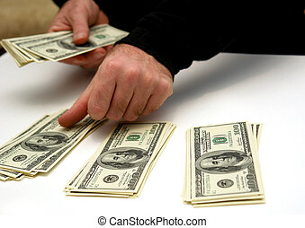 budgeting - man counting out hunderd dollar bills in three...