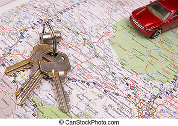 Map with keys and toy car - Red toy car on road map with...