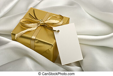 gift - golden present with a note on silver silk close up