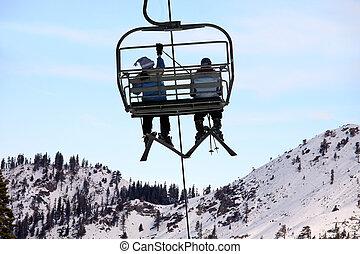 Skiers on chairlift at Lake Tahoe ski resort.