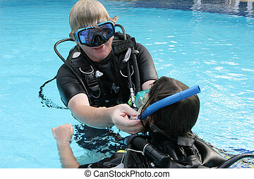 Scuba diving instructor demonstrates a skill to a student in...