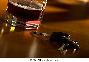 drunk driving - A set of car keys and glass of beer on a...