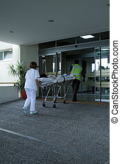 Paramedics carrying a patient in critical condition into a...