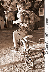 riding a bike - young boy in old style clothing rides a...