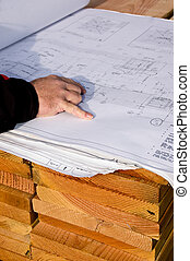 Blueprint - An architect at the job site, checking the...