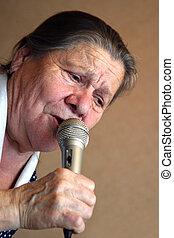 Karaoke - The elderly woman sings in karaoke