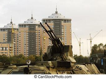 Guns of military vehicle against buildings in Kiev