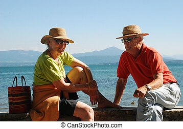 elderly couple - relaxing by lake