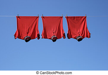 Laundry, red t-shirts - Laundry, three red t-shirts on a...
