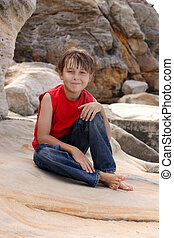 Happy child relaxes on rocks