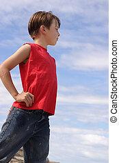Boy against blue cloudy sky