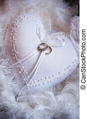 Wedding rings on a white textile heart