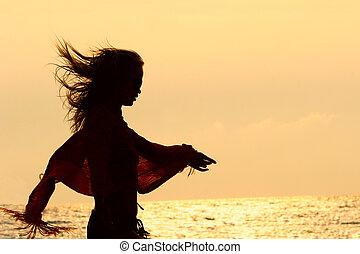 girl silhouette on golden sunset sky background
