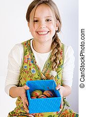 Young girl presenting a box with painted eggs - Studio...