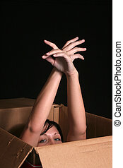 Woman emerging from box - A woman is emerging from a box