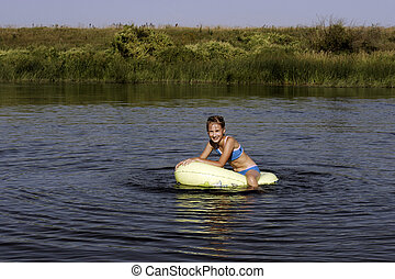 Girl on the boat - The Girl playing in water on inflatable...