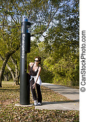 Knee Pain - A woman standing by an emergency call box...