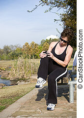 Knee Injury - A woman sitting on a park bench grasping her...