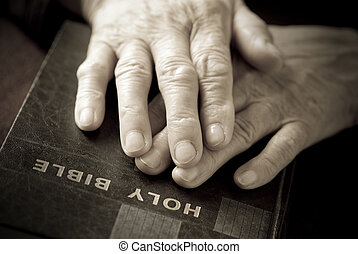 hands on the bible - special sepia toned and vignetting,...
