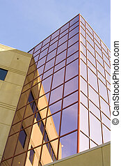 Tall office building with reflective pink glass windows -...