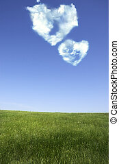 love concept - heart shapes on blue sky and fresh green...