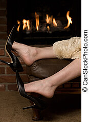 Warming feet - Womans legs removing high heel shoes in front...