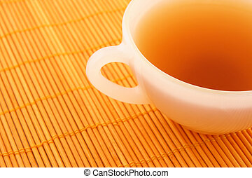Cup of tea on orange rattan mat in warm colors.