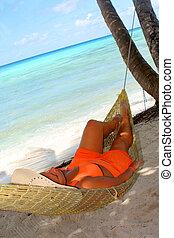 hammock beach woman - woman relaxing in a hammock on a...