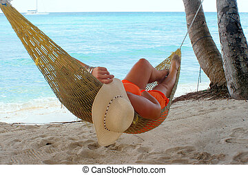 hammock beach woman - woman relaxing in a hammock on a...