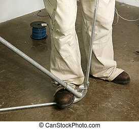 Electrical Pipe Bending - Closeup of electricians feet as he...
