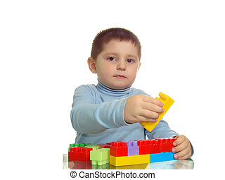 Boy playing with bricks looking to camera isolated