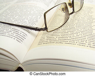 Glasses on an open  - Glasses lying on an open thick book