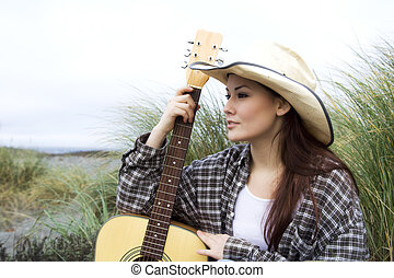 Guitar player - A beautiful girl posing with a guitar at the...